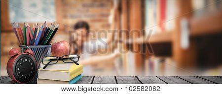 School supplies on desk against teacher and little girl selecting book in library