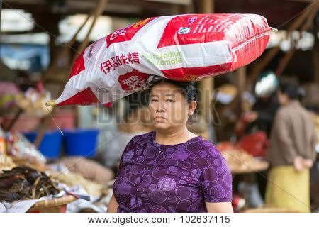 MANDALAY,MYANMAR,JANUARY 17, 2015: A woman is carrying a large monosodium glutamate bag on her head in the street of Mandalay, Myanmar (Burma).