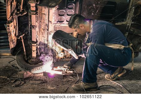 Young Man Mechanic Worker Repairing Old Vintage Car Body In Messy Garage - Safety At Work