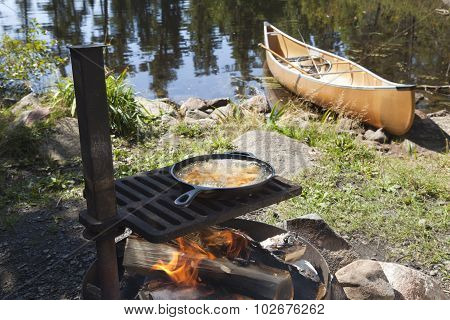 Fish Cooking Outdoors In A Frying Pan With A Canoe In The Background
