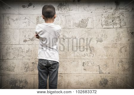 Young Young Asian boy standing facing a white wall