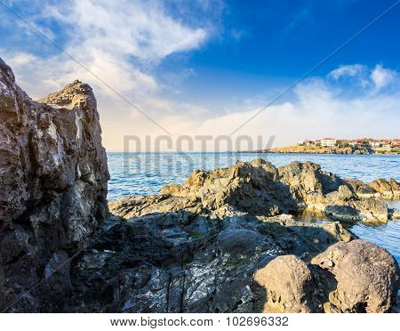 Sea Bay With Boulders And Old City At Sunrise