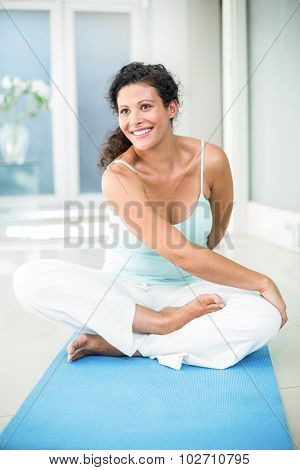 Full length of smiling pregnant woman stretching while sitting on exercise mat at home
