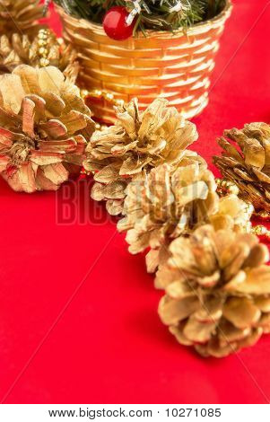 Christmas Fir-cones With A Gilt On A Red Background