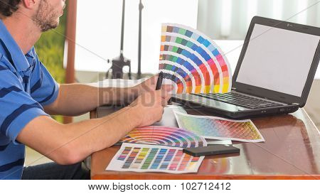 Male hands holding up palette, colormap spread out in front of laptop on working desk