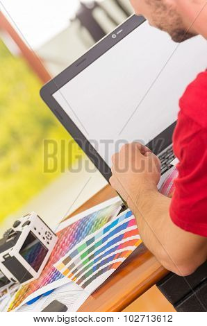Man working on laptop with palette, colormap spread out next to it