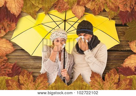 Couple sneezing in tissue while standing under umbrella against wooden background