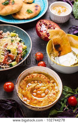 Table Served With Middle Eastern Vegetarian Dishes. Hummus, Tahini, Pitta, Couscous Salad And Butter