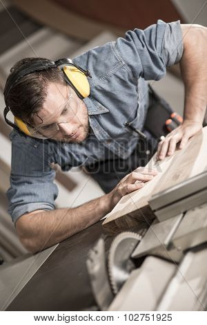 Joiner carefully cutting wooden plank with sawing machine poster