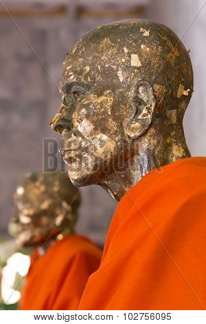 Profile view on a Buddha statue covered with golden leaves in the Wat Chalong Buddhist temple in Chalong, Phuket, Thailand