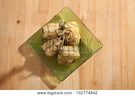 Ketupat (Rice Dumpling) On wooden Background. Ketupat is a natural rice casing made from young coconut leaves for cooking rice during eid Mubarak