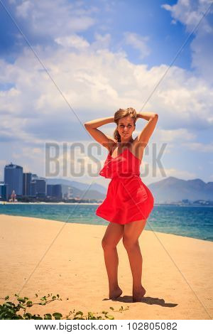 Blond Girl In Red Stands On Sand Puts Hands On Head Back