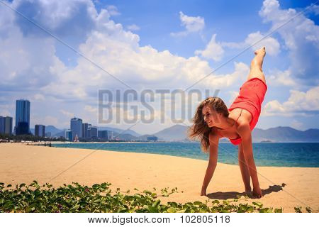 Blond Girl In Red Stands In Gymnastic Position Hands Leg Scale