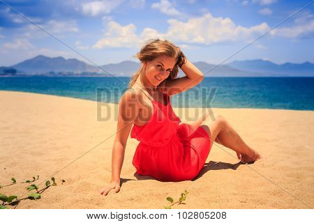 Girl In Red Sits On Sand Touches Hair Looks Downward Against Sea