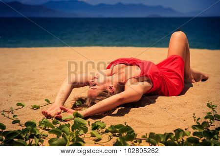 Upper View Blond Girl In Red Frock Lies On Sand Bends Knee
