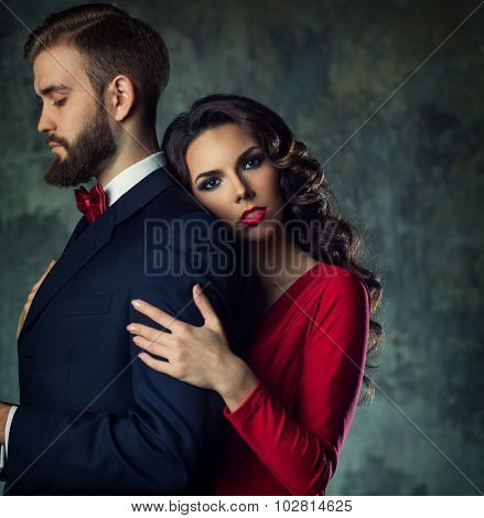 Young elegant woman embracing man. He is serious and looking aside. Quarrel concept. poster