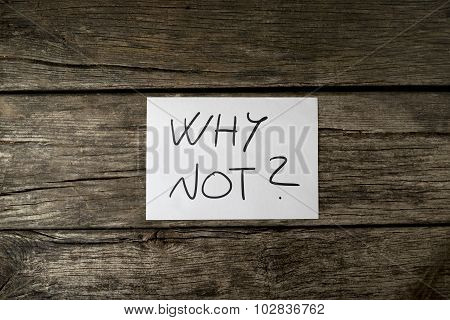 Overhead View Of White Card With Why Not Sign Lying On A Textured Rustic Wooden Desk
