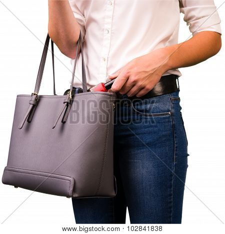 Girl puts a small bottle of nail varnish in her pocket