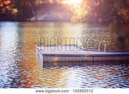 a serene view of a peaceful dock in a misty atmosphere on calm water during morning sunrise or evening sunset toned with a retro vintage instagram filter effect app or action