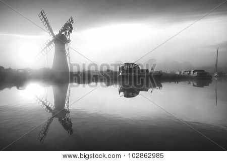 Stunnnig Landscape Of Windmill And Calm River At Sunrise In Black And White