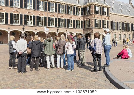 Guide with tourists on the Binnenhof in The Hague, Netherlands.