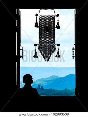 Neophyte At Window (in Partial Silhouette) With Thai  Hanging Mobile In A Public Temple, Wat Pa Phu