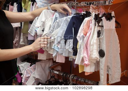 Young Woman Choosing Clothes For Child
