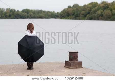 Lonely Teenage Girl With Umbrella Standing On River Dock On Gloomy Autumn Day