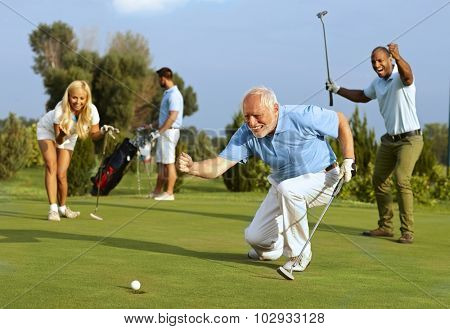 Happy senior golfer following golf ball to hole after putting. poster