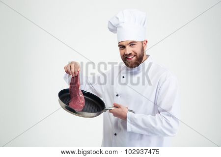 Portrait of a smiling chef cook holding pan with fresh meat isolated on a white background