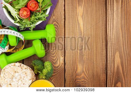 Dumbells, tape measure and healthy food over wooden table with copy space. Fitness and health