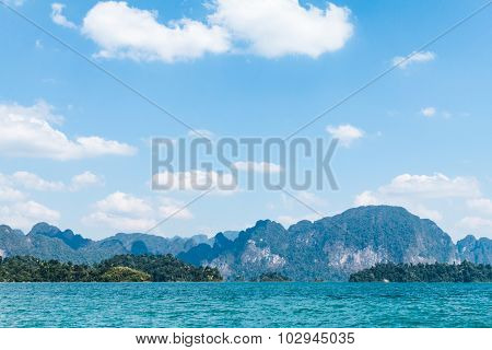 Blue clear water and blue sky with rock mountains reservoir lake at Ratchaprapa Dam Surat Thani Thailand