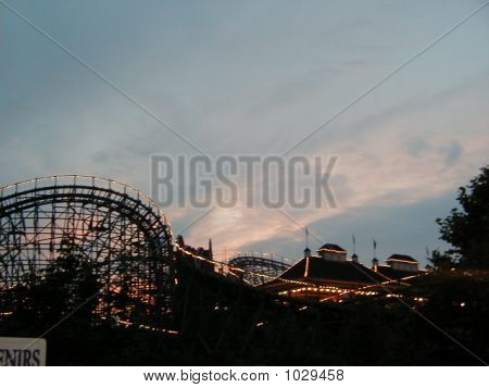 sunset at amusement park showing wild angles of the rides and clouds