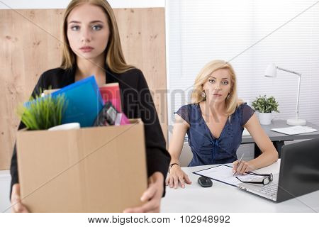 Boss dismissing an employee. Dejected fired office worker carrying a box full of belongings. Getting fired concept. poster