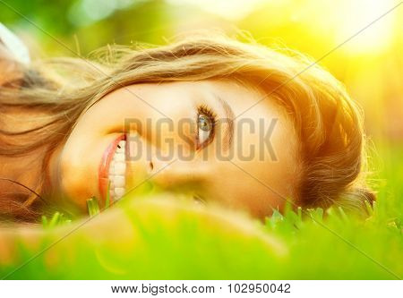 Beautiful teenage Girl lying on field of green grass close-up over sunlight. Outdoors. Model young woman smiling and enjoying nature outdoors. Cute Teenage Girl relaxing in the park. Sunshine