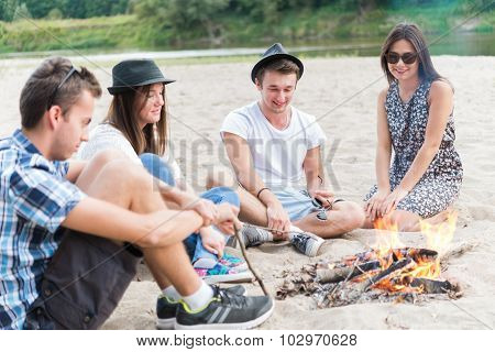 Four Friends Sitting At Bonfire On Sandy Beach