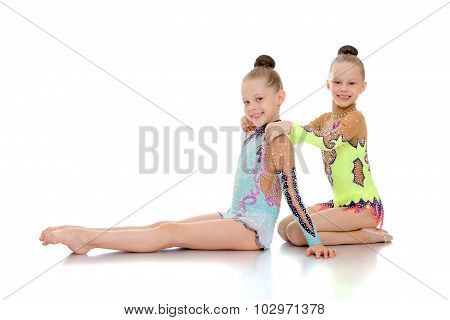 Adorable, beautiful little girls gymnasts sit leaning on each other. Synchronous movement . The girls are dressed in a smart sports swimwear-Isolated on white background poster