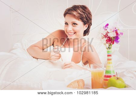 Happy lady having breakfast in bed