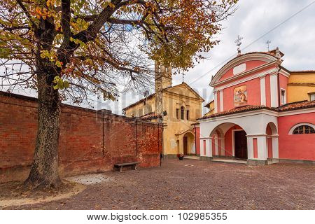 Two colorful churches on small cobblestone town square in town of Barolo in Piedmont, Northern Italy.