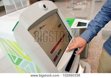 ROME, ITALY - AUGUST 16, 2015: people use self check-in kiosks in Fiumicino Airport. Fiumicino - Leonardo da Vinci International Airport is a major international airport in Rome, Italy