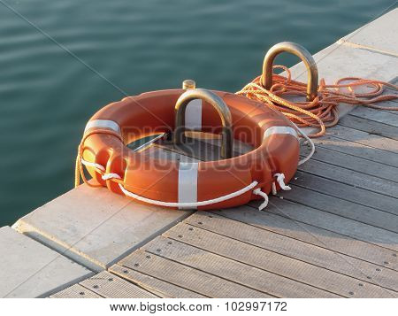Orange Life Buoy On Wooden Pier In The Harbor In Marina Di Pisa, Tuscany, Italy