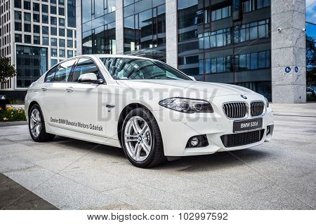 GDANSK, POLAND - SEPTEMBER 3 , 2015: New model BMW 520d in white against modern design buildings in Gdansk. BMW is a German automobile, motorcycle and engine manufacturing company founded in 1916.