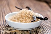 Heap of Brown Vanilla Sugar on wooden background poster