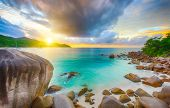 Beautiful sunset over the famous beach Anse Lazio seen from the granite boulders, Praslin island, Seychelles.  poster