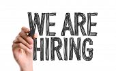 Hand with marker writing: We Are Hiring poster