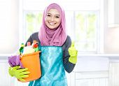 portrait of housewife wearing hijab holding bucket full of cleaning supplies and giving thumbs up with copy space poster