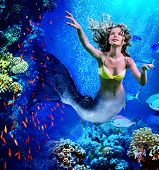 Girl mermaid dive underwater through coral fishes. poster
