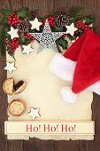 Letter to santa with ho ho ho sign, hat, silver christmas snowflake bauble decoration, holly and winter greenery on parchment paper over oak background. poster