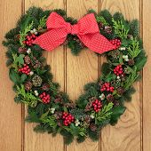 Christmas and winter heart shaped wreath with holly, mistletoe, red polka dot bow and greenery over oak background. poster