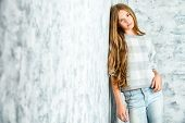 Pretty teenager girl in casual clothes posing over grunge background. Modern teen generation. Youth fashion. poster